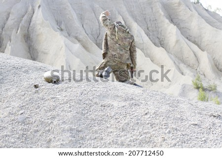 Desperate soldier in the desert need water - stock photo