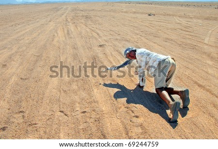 desperate thirsty tourist in Egyptian desert crawling over sand