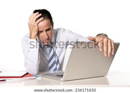 desperate tired senior businessman in crisis working on computer laptop at office desk in stress under pressure facing work problems isolated on white background - stock photo
