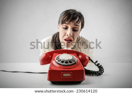 Desperate woman waiting for someone to call her - stock photo
