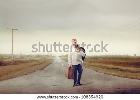 Desperate young businessman carrying a suitcase on a country road - stock photo
