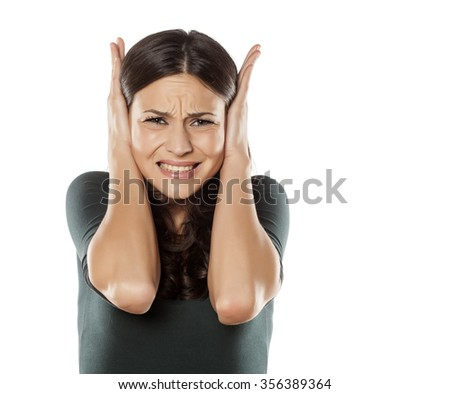 desperate young woman covering her ears because of the noise - stock photo