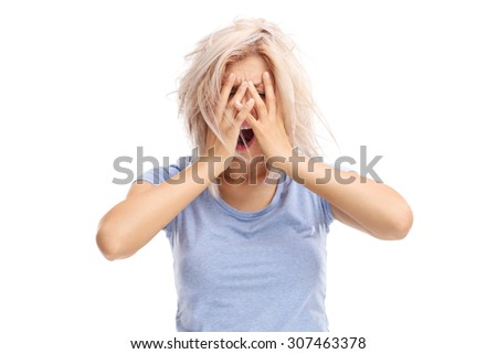 Desperate young woman holding her hands on her head isolated on white background - stock photo