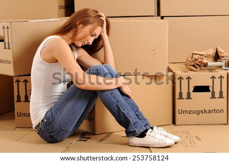 Desperate young woman with packing cases