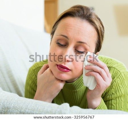 Desperately stressed woman on a sofa at home with a handkerchief in her hands and tears in her eyes