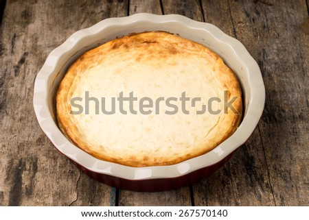 Dessert cooking background. Fresh baked cheesecake on wooden table. - stock photo