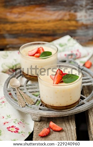 Dessert Cream - caramel in glass with strawberries on iron support and wooden background