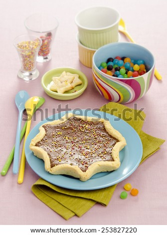 dessert for the holiday tart with chocolate in the shape of a star is decorated with colored utensils - stock photo