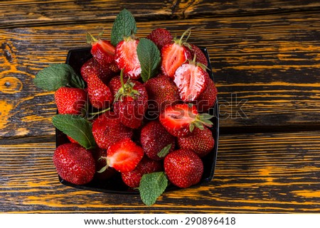 Dessert of delicious ripe red strawberries seasoned with fresh mint leaves and served on a rustic wooden table or counter top, overhead view - stock photo