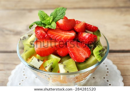 Dessert of fresh fruits in glass saucer on wooden table, closeup - stock photo