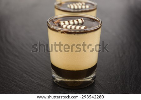 Dessert of panna cotta on a layer of espresso and topped with chocolate sauce. - stock photo