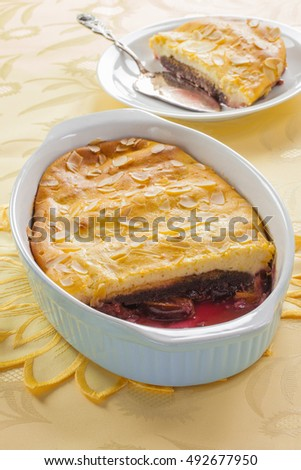 Dessert of prunes in syrup with biscuit and almonds in a ceramic tray with a checkered napkin on a yellow background, vertical