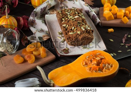 Dessert on Halloween. Homemade delicious cake with a pumpkin and dried apricots. Served on a wooden table with a plate, knife and fork. Horizontal image.