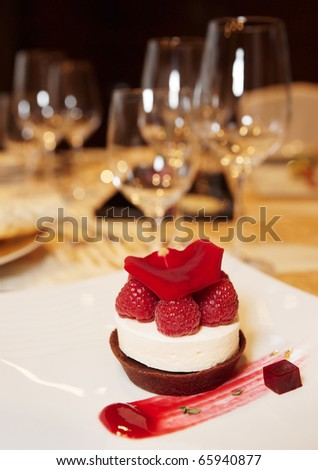 Dessert on plate in restaurant with wineglasses in blurred  background