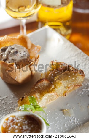 Dessert platter of creme brulee, nougat ice cream and apple tart paired with sweet wine.  - stock photo