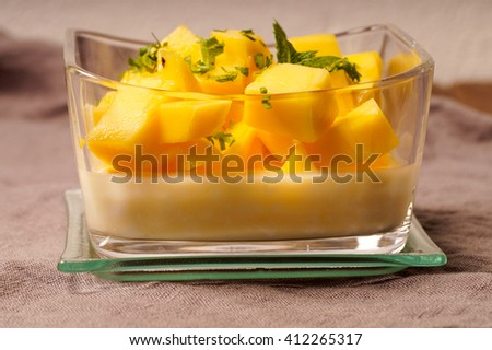 dessert pudding served with mango and chopped mint leaves