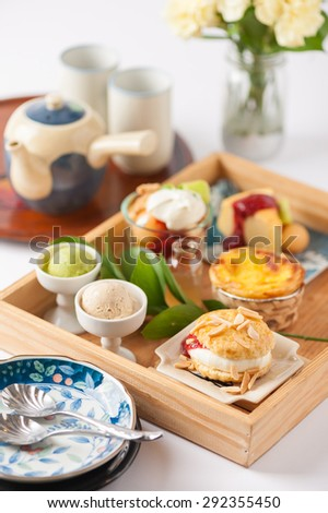 Dessert set for tea time with cake, ice cream, egg tart, and scone in wood tray with tea set and dishes - stock photo