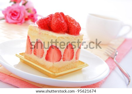 Dessert - sweet cake with strawberry on a plate with rose background - stock photo