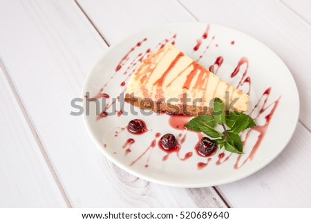 Dessert - sweet cheese cake with Cherry syrup decorated with fresh mint flavored