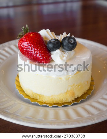 Dessert ,Sweet white cream cake with strawberry and berry topping on white plate. - stock photo