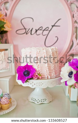 Dessert table for a party. Ombre cake and flowers