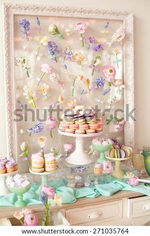 Dessert table with a macaroons composition - colorful pyramid, cupcakes, flowers