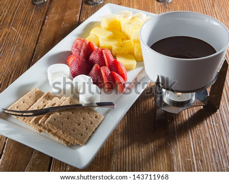 Dessert tray of fondue for two, with a carafe of melted chocolate over a warming candle and a metal dessert fork. - stock photo