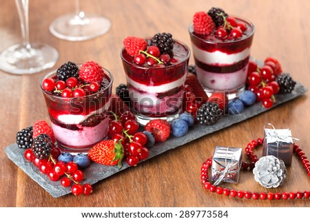 dessert with berries, Christmas decorations and champagne glasses   - stock photo
