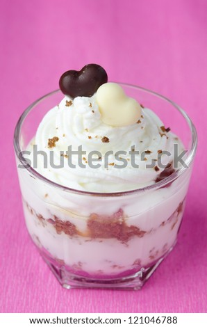 dessert with black bread, jam and whipped cream with chocolate hearts in a glass beaker on a pink background