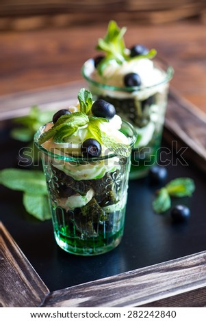 Dessert with matcha cake, cream cheese and berries in a glass beaker - stock photo