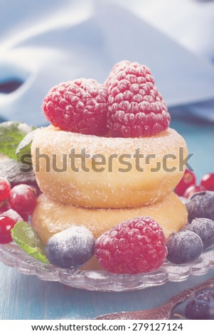 Dessert with mini donuts and berries on plate under powdered sugar on blue wooden background.  Tasty donuts closeup. Doughnut. Selective focus. Retro style toned. - stock photo