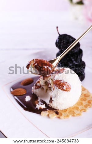 Dessert with prunes and ice cream with chocolate on plate and color wooden table background - stock photo