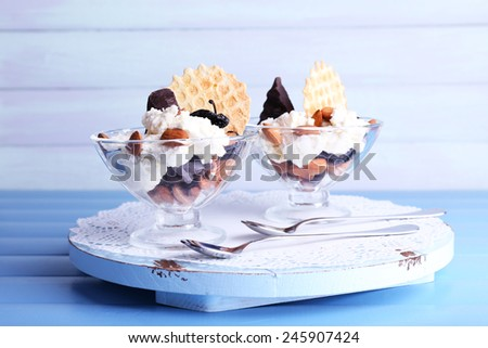 Dessert with prunes in glass bowls on color wooden table background - stock photo
