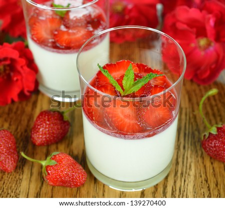 Dessert with strawberries in a glass on a brown table