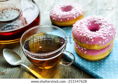 Dessert with sweet pink doughnuts, teapot and cup of tea - stock photo