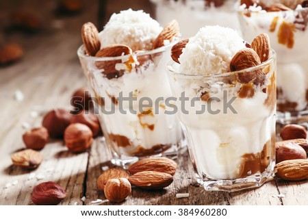 Dessert with vanilla ice cream, nut sauce, almonds, hazelnuts and coconut, served in glasses, selective focus - stock photo