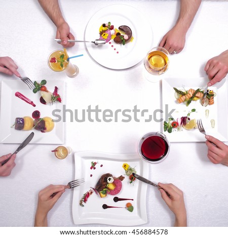 Desserts and drinks symmetrically served on white table with bright decorations and human hands - stock photo