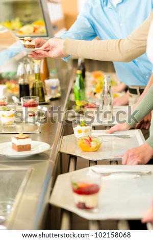 Desserts at cafeteria people with serving tray self service canteen