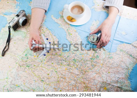 Destination points. A woman sitting at table with a map, airplane, compass and camera and visualises his desire to travel.  Top view. Globetrotter coffee break for trip dreams. - stock photo