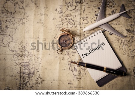 Destination word and old brass compass on wood table top view