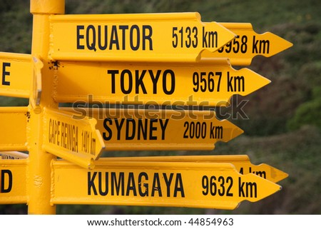 Destinations in New Zealand - variety of direction signs in Bluff - stock photo