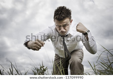 Destined for success. Young man in combat posture compresses his fists ready to strike. He fights for his success. Brave youth. - stock photo