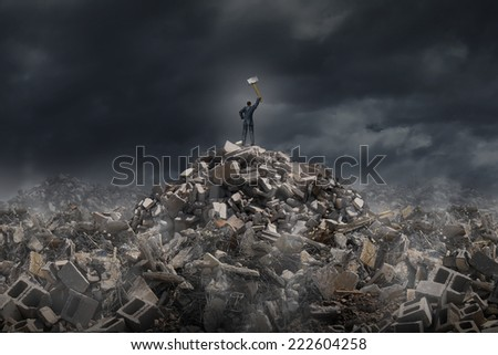 Destroy and demolish concept as a businessman standing on a mountain of  building ruins holding a sledge hammer as a business or life metaphor for tearing down old industry for modern infrastructure. - stock photo