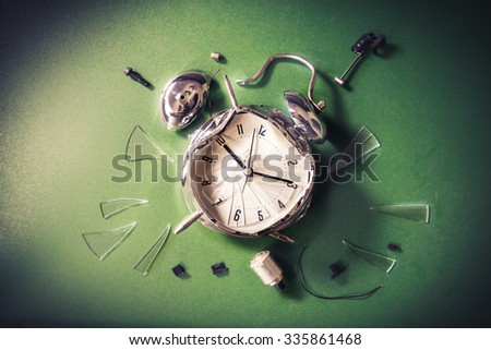 Destroyed alarm clock on a chalkboard / late for school concept - stock photo