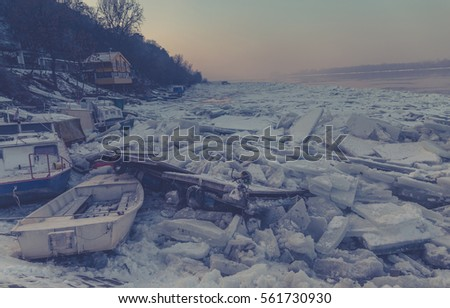Destroyed boats on a frozen Danube river with lots of ice cubes and fantastic sunset near Belgrade, Zemun, Serbia, haze effect