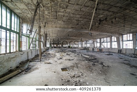 Destroyed interior of factory hall with great mess contains broken things around. Creative photography by using wide angle lens. - stock photo