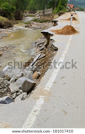 Destroyed road after natural disaster of river flooding - stock photo