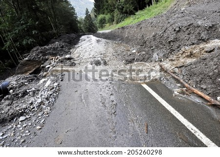 Destroyed rural road landslide damaged in powerful flood. Collapsed road on the mountain - stock photo