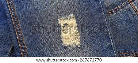 Destroyed torn denim blue jeans with orange thread seams  - stock photo