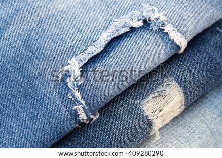 Destroyed torn denim blue jeans with patch, close up, Flat Lay - stock photo